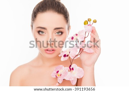 Portrait of sensetive young woman with orchid on white background - stock photo