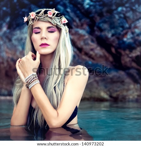 Portrait of sensual blond girl in a wreath in the sea - stock photo
