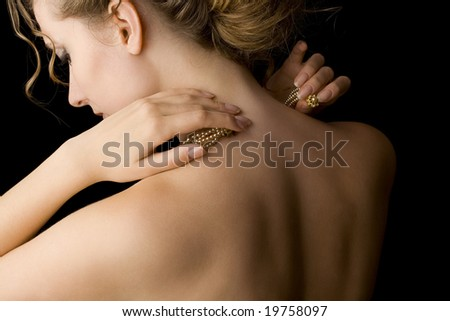 portrait of sensual blond woman putting on pearls; luxury accessories - stock photo
