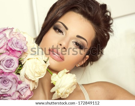 Portrait of sensual brunette beautiful woman with flowers. Lady in perfect makeup.