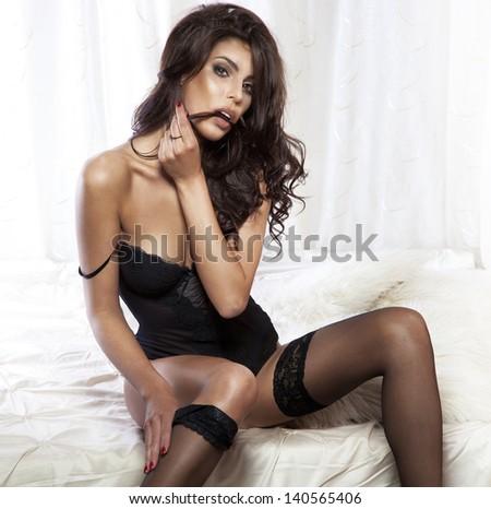 Portrait of sensual brunette woman wearing sexy black lingerie , posing in bedroom. - stock photo