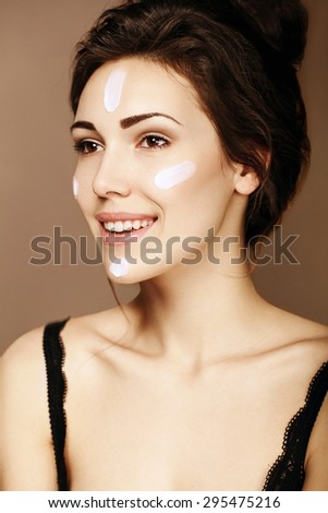 Portrait of sensual woman applying moisturizing cream on her face. Beauty, spa, wellness - stock photo