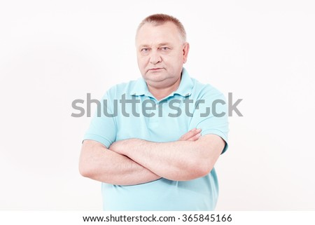 Portrait of serious aged man wearing blue shirt standing with crossed arms against white wall - retirement concept - stock photo