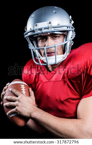 Portrait of serious American football player holding ball against black background