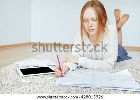 Portrait of serious and concentrated student girl busy working on diploma work at home, using digital gadget, lying on the floor. Thoughtful redhead freckled teenage female making notes in her diary  - stock photo