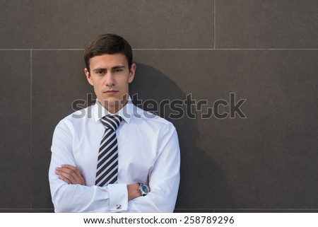 Portrait of serious and confident adult businessman wearing shirt and necktie with arms crossed in front of gray wall with copyspace - stock photo