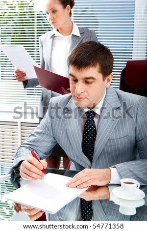 Portrait of serious boss going to sign contract while executive secretary standing near by - stock photo