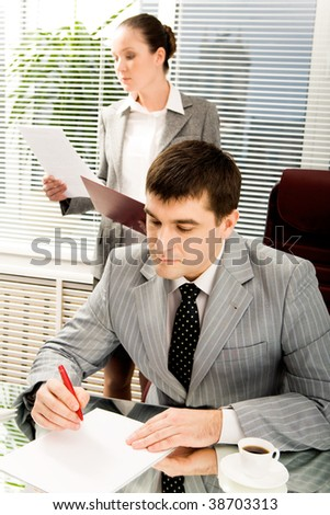 Portrait of serious boss signing contract with executive secretary on background