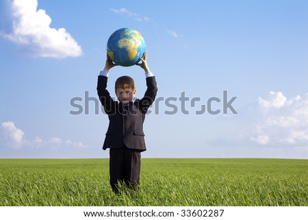 Portrait of serious boy holding globe in summer