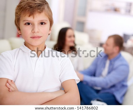 Portrait of serious boy looking at camera on background of his parents - stock photo