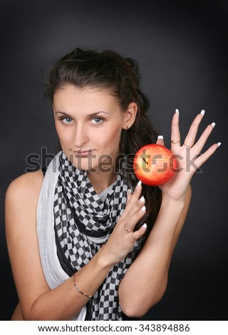 Portrait of serious brunette with a red apple in a hand. Witch, fortune-teller, astrology, forecaster - stock photo