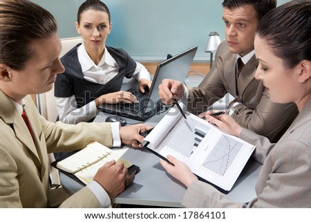 Portrait of serious business group looking at their partner in the office - stock photo