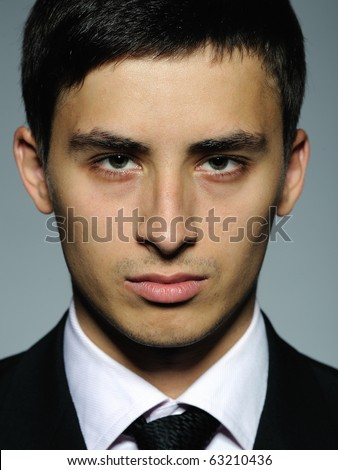 Portrait of serious business man in formal suit and black tie . expressions on gray background