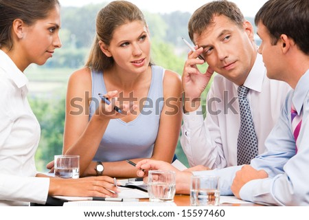 Portrait of serious business partners looking at man explaining new idea and listening to him - stock photo