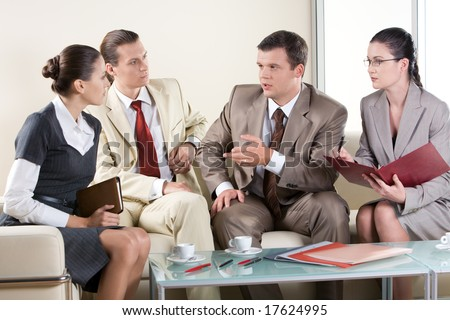 Portrait of serious business people sitting next to each other and communicating at business meeting - stock photo