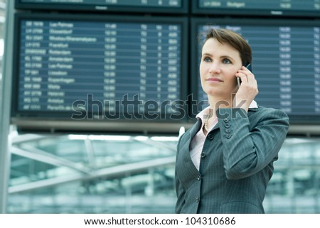 Portrait of serious business woman on mobile phone in front of panel at airport - stock photo