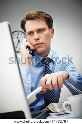 Portrait of serious businessman looking at laptop screen while calling by cellphone - stock photo