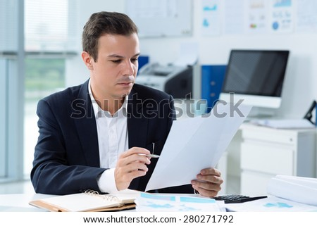 Portrait of serious businessman reading a document