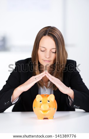 Portrait of serious businesswoman joining fingers above piggy bank at desk - stock photo
