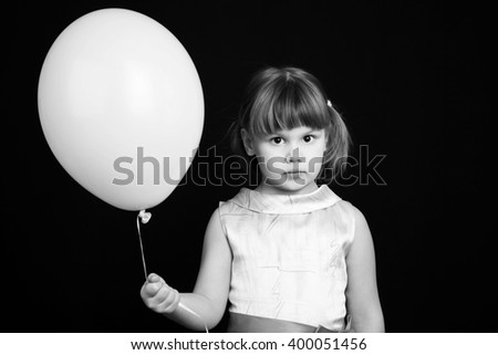 Portrait of serious Caucasian blond little girl with white balloon - stock photo