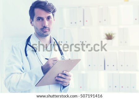 Portrait of serious doctor holding his clipboard and taking notes. Concept of general practitioner. Toned image