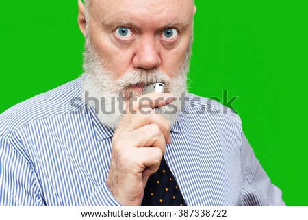 Portrait of serious elderly man speaking to voice recorder on green background, color and contrast manipulated - stock photo