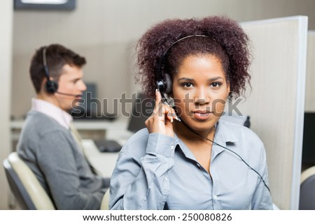 Portrait of serious female customer service representative using headset with male colleague in background at office - stock photo