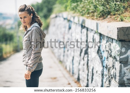 Portrait of serious fitness young woman in the city park - stock photo