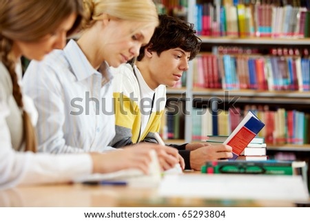 Portrait of serious groupmates preparing lessons in college library - stock photo
