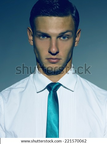 Portrait of serious handsome young man in casual white shirt and blue tie. Stylish haircut. Hipster style. Studio shot - stock photo