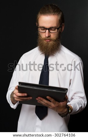 Portrait of serious hipster bearded businessman with documents. Boss in glasses posing in  business suit on black background. - stock photo