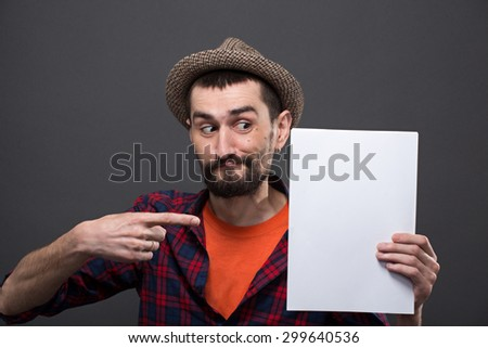 Portrait of serious hipster bearded man pointing out. Handsome man in hat keeping A4 sheet of blank paper in his hand. - stock photo