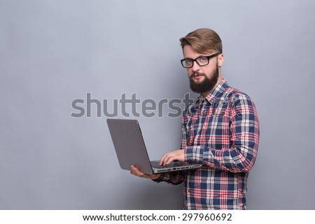 Portrait of serious hipster bearded man with laptop. Man in glasses typing document and looking at the camera isolated on grey. - stock photo