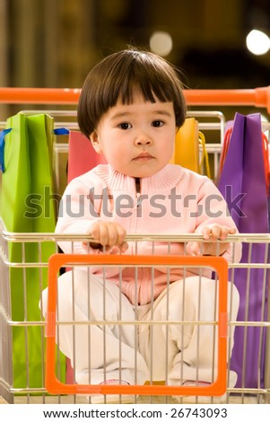Portrait of serious infant sitting in the handcart and looking at camera - stock photo