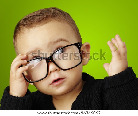 portrait of serious kid wearing glasses and doing a gesture over green - stock photo