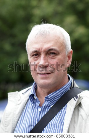 Portrait of serious man in the park - stock photo