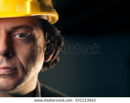 Portrait of serious middle aged man working as construction worker with hardhat. Copy space - stock photo