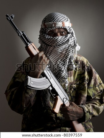 Portrait of serious middle eastern man with AK-47 - stock photo