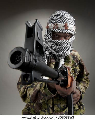 Portrait of serious middle eastern man with AK-47 aiming to you