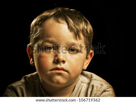Portrait of serious, sad, angry or depressed child isolated on black - stock photo
