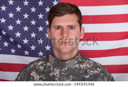 Portrait Of Serious Solider Standing In Front Of Us Flag