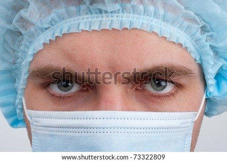 Portrait of serious surgeon in surgical mask and hat
