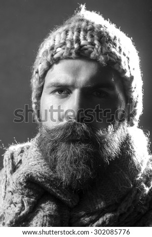 Portrait of serious unshaven male tramp with long beard and hendlebar moustache in knitted hat and scarf looking forward black and white closeup, vertical picture