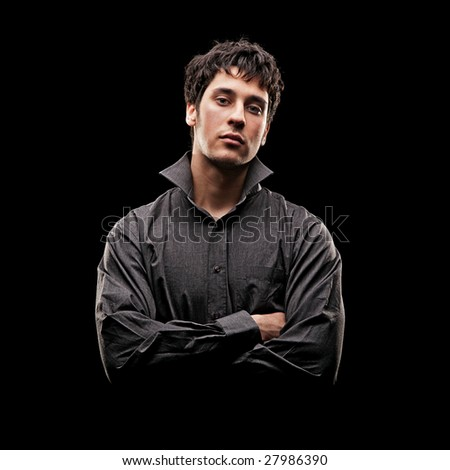 portrait of serious young man in shirt against black background - stock photo