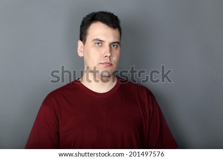 Portrait of serious young man in vinous T-shirt - stock photo