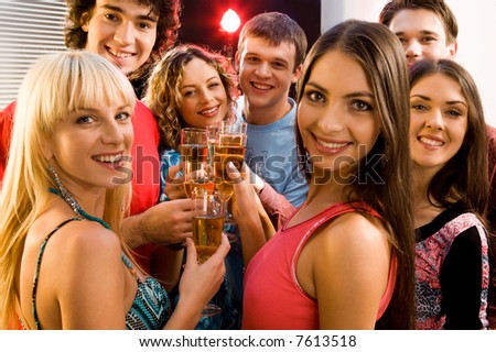 Portrait of seven friends holding glasses of champagne - stock photo