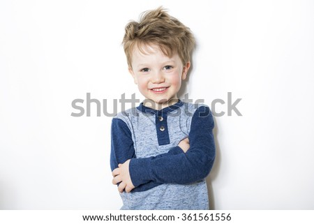 Portrait of seven years old boy on gray background