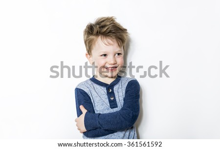 Portrait of seven years old boy on gray background - stock photo