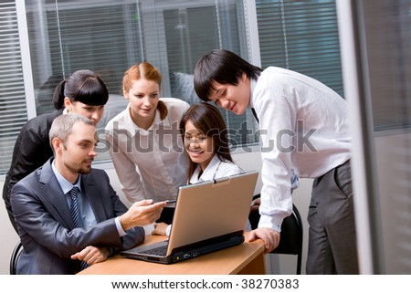 Portrait of several colleagues looking at laptop screen in the office