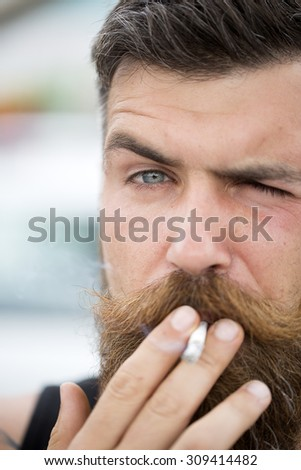 Portrait of sexual attractive unshaven man with beard and handlebar moustache smoking cigarette looking forward with expressive face outdoor closeup, vertical picture - stock photo